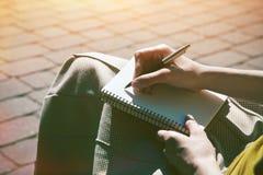 Manos con la escritura de la pluma en el cuaderno foto de archivo