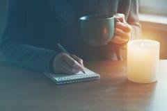 Manos con la escritura de la pluma y del té o del café en el cuaderno Imagen de archivo