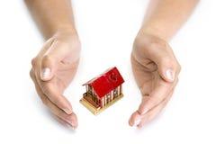 Manos con la pequeña casa - concepto de la mujer de los bienes inmuebles Imágenes de archivo libres de regalías