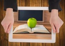 Manos con la tableta en la tabla que muestra el libro con la manzana verde Fotos de archivo libres de regalías