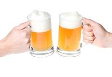 Manos con la taza de aclamaciones de la cerveza foto de archivo libre de regalías