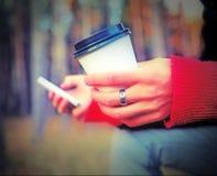 Manos con la taza de café y el teléfono móvil Imagenes de archivo
