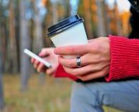 Manos con la taza de café y el teléfono móvil Foto de archivo