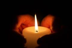 Manos con la vela ardiente Fotos de archivo libres de regalías