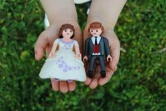 Manos con las figuras de la boda Imagen de archivo libre de regalías