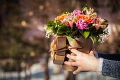 Manos con las flores en la caja Foto de archivo