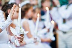 Manos con las velas de niñas en la primera comunión santa Fotografía de archivo libre de regalías