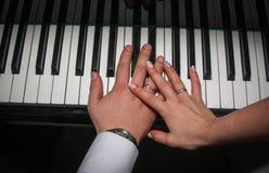Manos con los anillos de bodas en el piano Foto de archivo libre de regalías