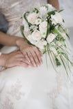 Manos con los anillos de bodas y el ramo Imagenes de archivo