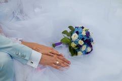 Manos con los anillos de bodas y el ramo de la boda Imagen de archivo libre de regalías