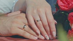 2 manos con los anillos de bodas y ramo en la tabla metrajes