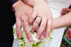 Manos con los anillos de compromiso en ramo nupcial Fotografía de archivo libre de regalías