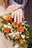 Manos con los anillos de compromiso en ramo nupcial Foto de archivo libre de regalías