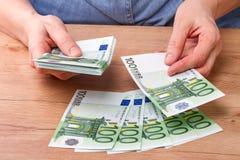 Manos con los billetes de banco de 100 euros Imágenes de archivo libres de regalías