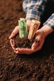 Manos con los billetes de banco del dinero del suelo fértil y del euro Imagenes de archivo
