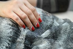 Manos con los clavos manicured artificiales largos coloreados con el esmalte de uñas rojo Fotos de archivo
