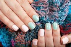 Manos con los clavos manicured cortocircuito coloreados con el esmalte de uñas rosado y verde fotos de archivo