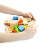 Manos con los juguetes de madera del bloque Imágenes de archivo libres de regalías