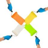 Manos con los rodillos sumergidos en colores brillantes Fotografía de archivo