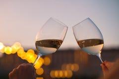 Manos con los vidrios de vino blanco que comprueban calidad de vino en la puesta del sol Fotografía de archivo libre de regalías
