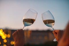 Manos con los vidrios de vino blanco que comprueban calidad de vino en la puesta del sol Fotos de archivo