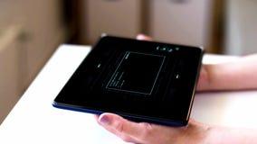 Manos con PC de la tableta con la codificación en la pantalla almacen de metraje de vídeo