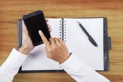 Manos con smartphone y orden del día Imagen de archivo libre de regalías