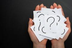 Manos con una nota escrita por un signo de interrogación en el fondo fotografía de archivo libre de regalías