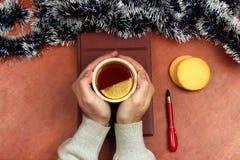 Manos con una taza de té en la tabla de la oficina antes del Año Nuevo Imágenes de archivo libres de regalías