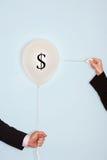 Manos cosechadas que sostienen la aguja y que hacen estallar el globo con símbolo del dólar imágenes de archivo libres de regalías