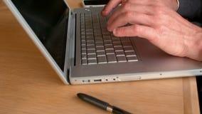 Manos de Businessmans que mecanografían en el teclado del ordenador portátil almacen de video