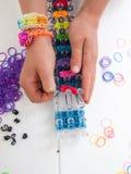 Manos de Childs con el telar y las bandas elásticas multicoloras Fotografía de archivo