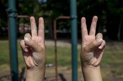 Manos de Childs que hacen signos de la paz Imagenes de archivo