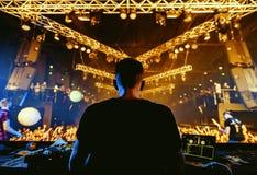 Manos de DJ para arriba en el partido del club de noche bajo luz azul con la muchedumbre de gente Fotos de archivo
