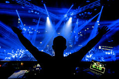 Manos de DJ para arriba en el partido del club de noche bajo luz azul con la muchedumbre de gente Fotografía de archivo