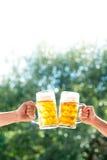 Manos de dos hombres que sostienen las tazas de cerveza fotos de archivo