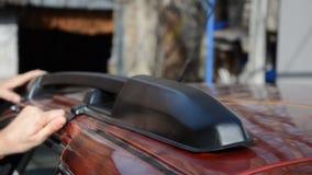 Manos de dos varones que desatan los tornillos y que quitan la verja negra del coche de un tejado del coche almacen de video