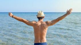 Manos de extensión del hombre en la playa Fotografía de archivo libre de regalías