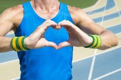 Manos de Holding Up Heart del atleta Imagenes de archivo