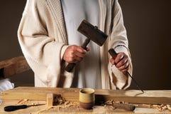 Manos de Jesús con las herramientas del carpintero Imagen de archivo