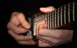 Manos de jugar del guitarrista foto de archivo