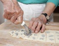 Manos de la abuela en la hornada Foto de archivo libre de regalías