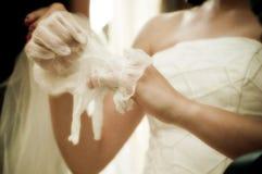 Manos de la boda y el poner en guante Fotografía de archivo