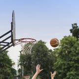 Manos de la bola del baloncesto del jugador que lanza en cesta Juego de baloncesto de la calle Escudo, cesta y bola del baloncest Fotos de archivo