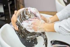 Manos de la cabeza que se lava del cosmetólogo Fotografía de archivo libre de regalías