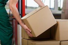 Manos de la caja de elevación del trabajador del almacén