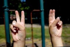 Manos de la chica joven/de las hembras bajo la forma de gesto de mano para la paz foto de archivo