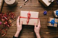 Manos de la cosecha que llevan a cabo el presente envuelto en la tabla Imagen de archivo libre de regalías