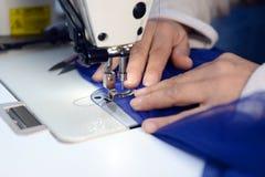 Manos de la costurera en la máquina de coser Imagenes de archivo