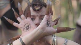 Manos de la dríada o de la hada del bosque con los ojos pintados en las palmas y las garras falsas que bailan y que cubren la car almacen de metraje de vídeo